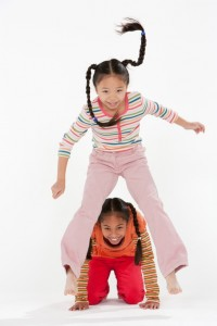 Two girls playing leap frog